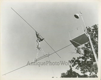 Woman tightrope chair cycling balancing act vintage acrobat circus photo