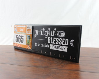 Running medal holder and race bib display featuring the inspiring graphic - grateful and Blessed to be on this Journey