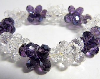 This bracelet is made up of clusters of 9 faceted clear, and Royal purple beads.