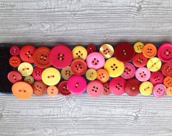 Handmade pink and orange button cuff bracelet on denim