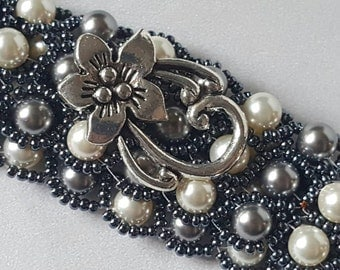 A headband made of 117 gray and cream Swarovski Crystal pearls wrapped in dark gray seed beads, with a silver flower option