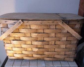 Rustic picnic basket made with woven split oak.  Has a hinged lid and measures 19 inches long 11 inches wide and 11 inches deep