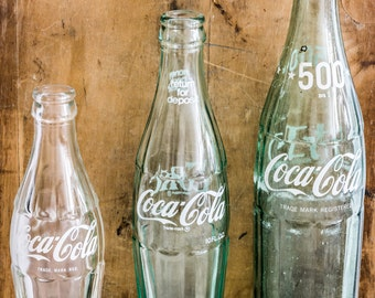 A set of Three (3) Vintage Coca Cola Bottles in three different sizes