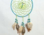 13.5cm diameter blue and lime green dreamcatcher with feathers and a central butterfly.