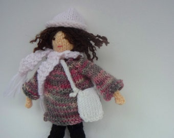 tiny knitted doll in outdoor clothes