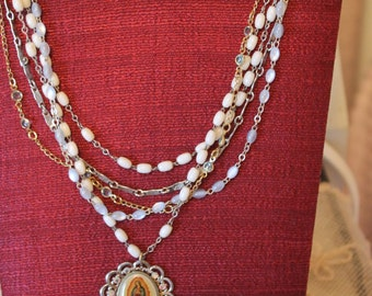 Multi Strand Chained Necklace Holding Religious Charm