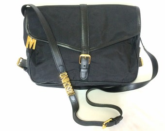 MINT. Vintage Moschino black nylon saumur messenger shoulder bag with leather trimmings with M logo charm. Produced by Redwall.