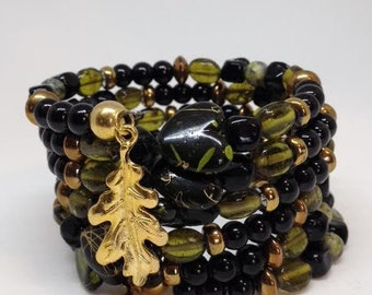 Green, black and gold cuff memory wire bracelet with leaf charms