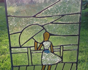 Glass panel of a Girl with beaded turquoise belt is  caught in inclement weather