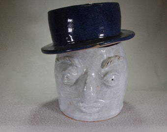 White stoneware face pot with mustache and a dark blue slouchy top hat lid.