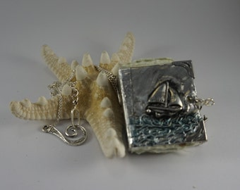 Sailing on calm seas, a miniature hand embossed metal book for you to write in