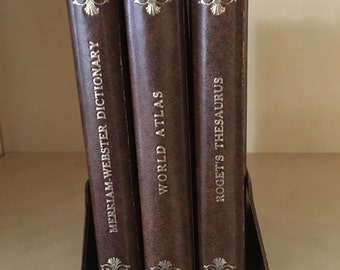 Merriam Webster dictionary 1963 plus a Rand Mcnally world atlas 1964 plus a Roget's thesaurus 1965 collection in holder