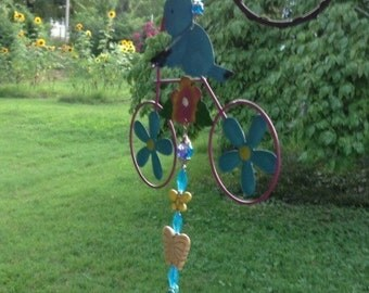 Reimagined Hand beaded bird on bike into metal yard art suncatcher