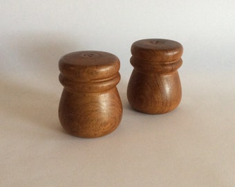 Wooden salt and pepper shakers with plastic stoppers on the base.