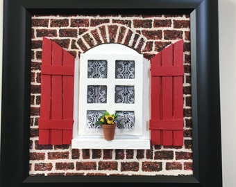 Painting of red window on brick house