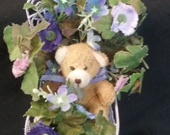 Small bear in purple chair covered in lavender and purple flowers