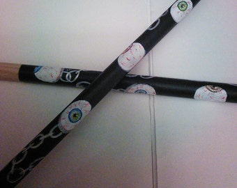 Drum sticks with a eyeball and chain theme