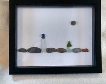 Lighthouse and sailboat. Pebble and seaglass art.