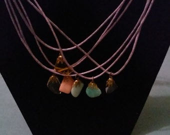 Plastic stone chips hung on a purple hemp necklace