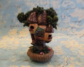 Miniature fairy tree house in an acorn cap