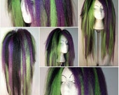 A pair of Loose hair falls in neon green, purple and black. Massive hair!