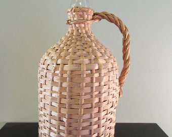 Vintage wicker covered glass bottle with screw on cap and wicker handle- nice condition, beautiful, great home decor