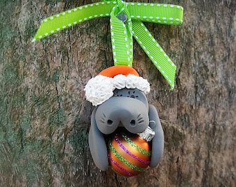Santa Manatee Holding Orange Christmas Ball Ornament
