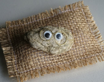 Pet rock wearing glasses with natural expression and burlap pillow bed