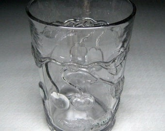 eapg glass tumbler with cherries , reads 9 AV OZ on the bottom edge , has cherries on the bottom