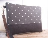 Large wristlet made with a modern european star fabric in gray and gray linen , this wristlet has a brown leather strap .