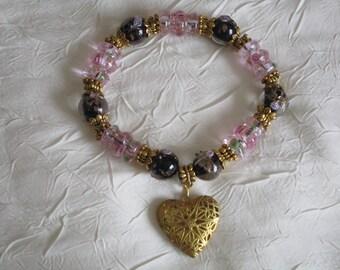 Bracelet en perles lampwork rose et noires avec un gros coeur doré