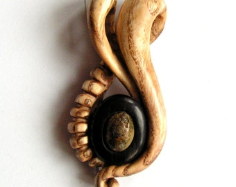Delicate hand carved wooden pendant with natural Baltic amber