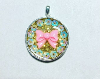 Resin pendant with pink bow and gold glitter.