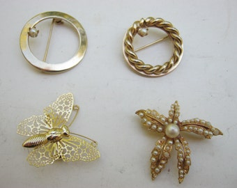 4 small gold colored Brooches/Pins