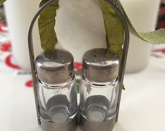Glass salt and pepper shakers in a metal holder