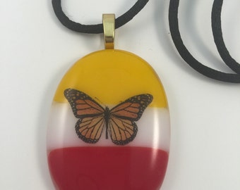 Stripes of yellow, white and orange with a colorful butterfly accent fused glass pendant