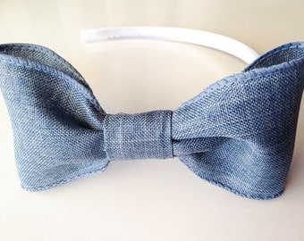 White Satin covered hard headband with an adorable large light denim blue bow for baby and girls