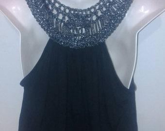 Black crop top sliver and black glittered crochet on back.