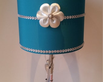 Girly Glam Lamp with teal lamp shade, white floral embellishment, crystal-like flower rhinestone border & centre trim. Pretty and elegant!