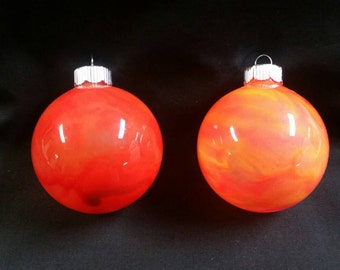 2 glass ornaments the shades of orange and pink swirls