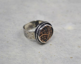 Wide patterned square band ring with old copper coin.
