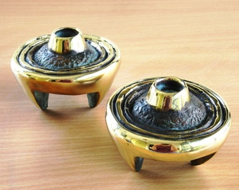 A pair of cast brass designed candle holders