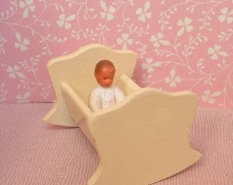 Vintage dollhouse rocking cradle.