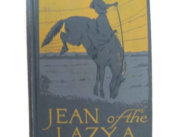 """vintage book """"Jean of the Lazy A"""" with a cowgirl 'let 'er buck!' cover, 1916."""