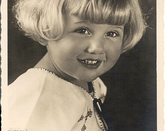 Little blondie, cute girl with sweet smile, embroidered smock, c1940s photo, deckled edge postcard, supply ephemera