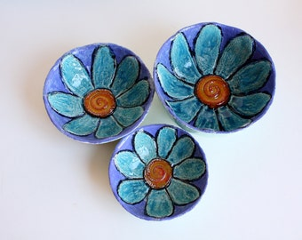 Three ceramic bowls decorated with a flower