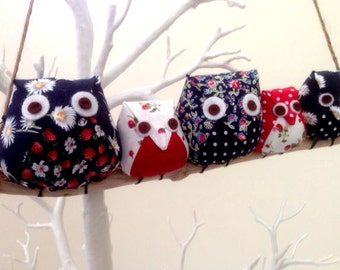 Owl family on a branch, 5 red,blue and white owls