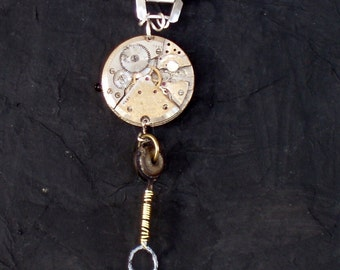 Industrial designed pendant necklace featuring vintage watch parts, wire wrapped parts and silver beads.