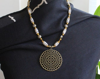 Bronze colored pendant with domino beaded enchancements