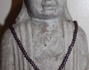 The purple beaded necklace, with a purple crystal